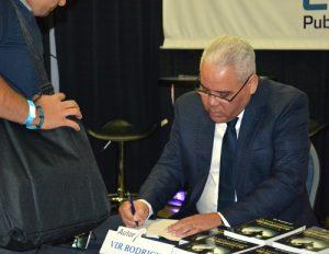 Vir Rodríguez, de Panamá, firma al público copias de su libro De Saint Germain a Jesucristo.
